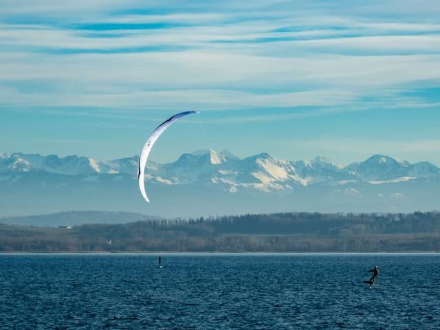 Ein Kitesurfer mit einem Mattenkite und einem Foil unterwegs auf einem See.