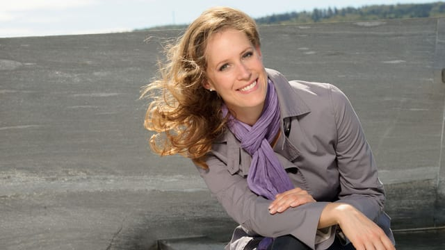 Daniela Schmuki trägt einen grauen Mantel und lächelt mit wehendem Haar in die Kamera.