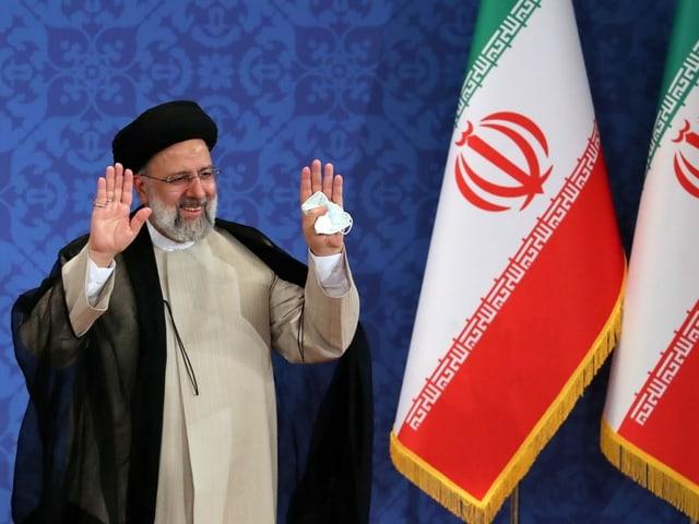 Ebrahim Raisi grüsst an der Pressekonferenz und hebt beide Hände in die Luft.
