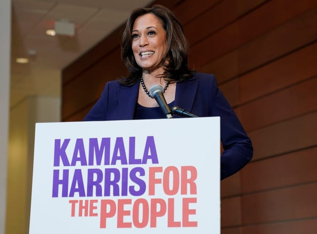 Kamala Harris mit einem Wahlkampf-Plakat.