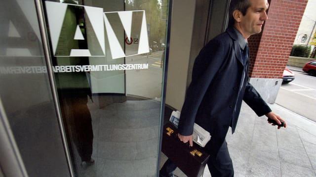 Älterer Mann in Anzug mit Aktenkoffer verlässt ein Arbeitsvermittlungszentrum durch eine Glastüre