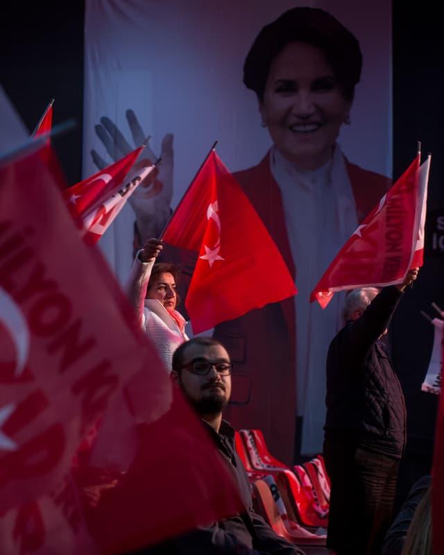 Anhänger halten Türkei-Fahnen hoch vor einem überlebensgrossen Bild von Aksener.