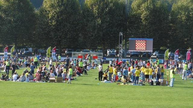 Man sieht viele Schüler und Schülerinnen, die auf dem Sportplatz stehen und sitzen und auf die Grossleinwand schauen