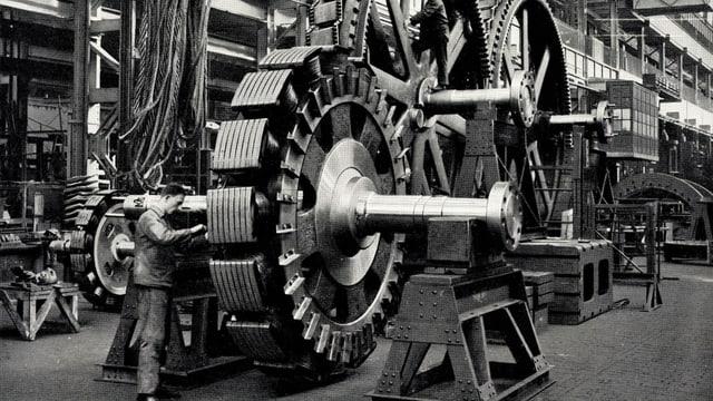 Ein Mann steht neben einer grossen Maschine mit riesigen Zahnrädern.