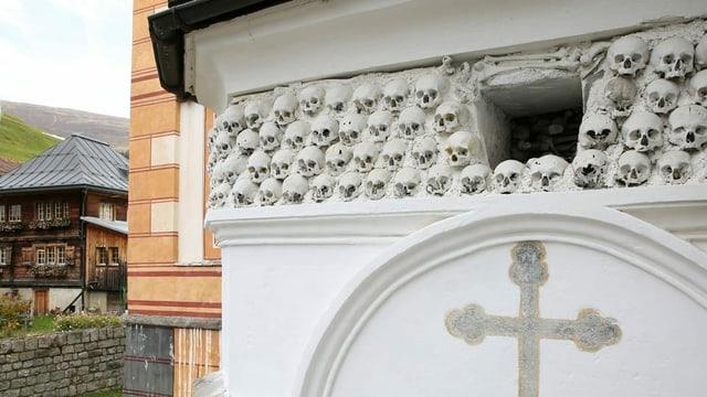 An der Wand eines kirchengebäudes sind Totenschädel eingemauert