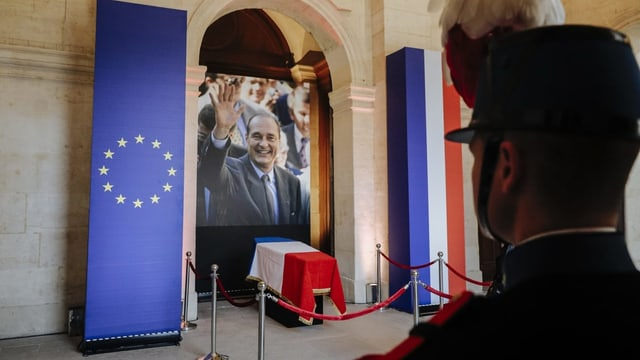 Sarg des Präsidenten in einer Nische. Darum herum die Fahne Frankreichs und der EU. Dahinter ein Fotos Chiracs.