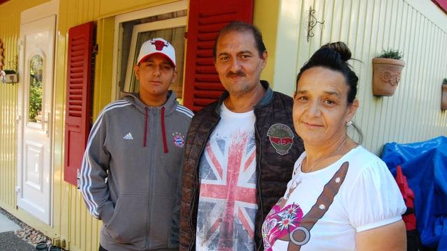 Familie vor einem kleinen Haus