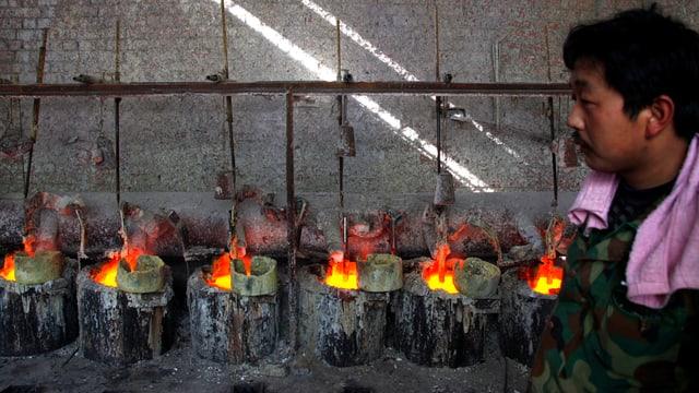 Ein Arbeiter in einer Fabrik in der Mongolei überwacht Behälter, die das Seltene-Erden-Element Lanthanum enthalten.