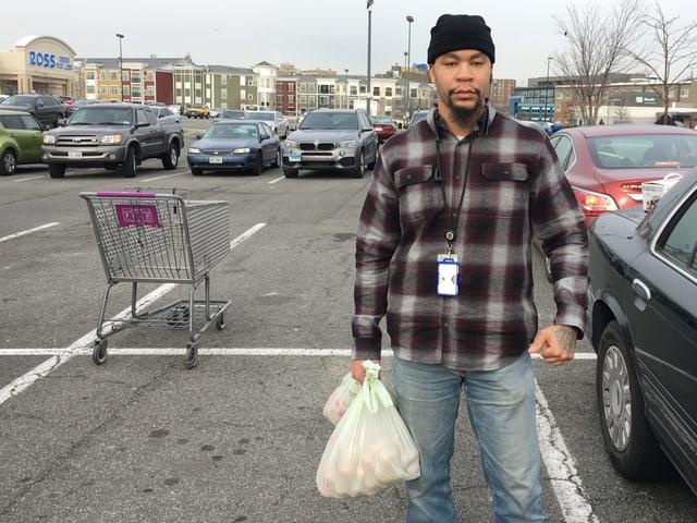 Mann mit Lebensmitteln in der Hand auf einem Parkplatz