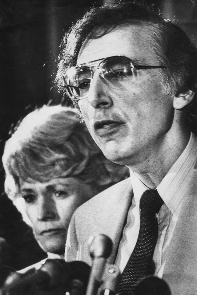 Ein Mann mit Brille und eine Frau stehen vor einem Mikrophon