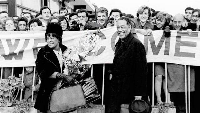 """Ella Fitzgerald und Duke Ellington stehen lächelnd vor einer Schar Leuten, die ein grosses """"Welcome""""-Banner vor sich tragen."""