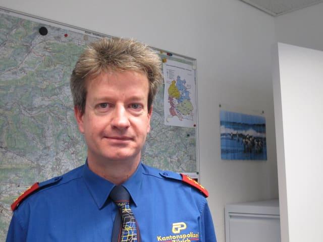 Ein Polizist mit hellbraunen haaren und blauer Uniform vor einer Landkarte.