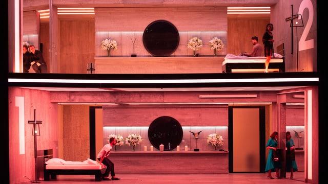 Eine zweistöckige Bühne, mit zwei Wohnungen, die rosa ausgeleuchtet sind.