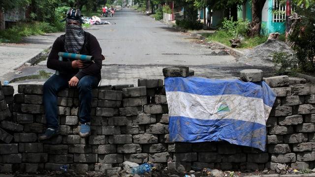 Ein Mann mit einer selbstgebauten Waffe sitzt auf einer Strassenblockade