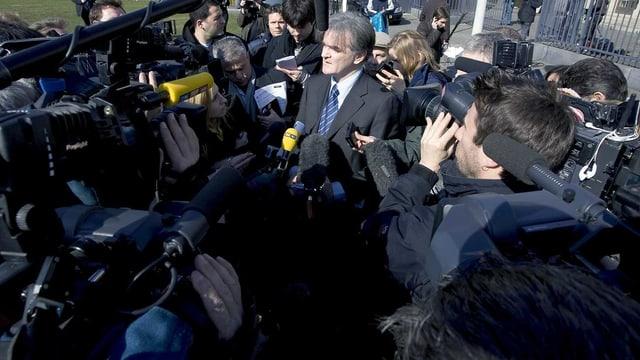 Ein Anwalt wird von Presseleuten umzingelt.