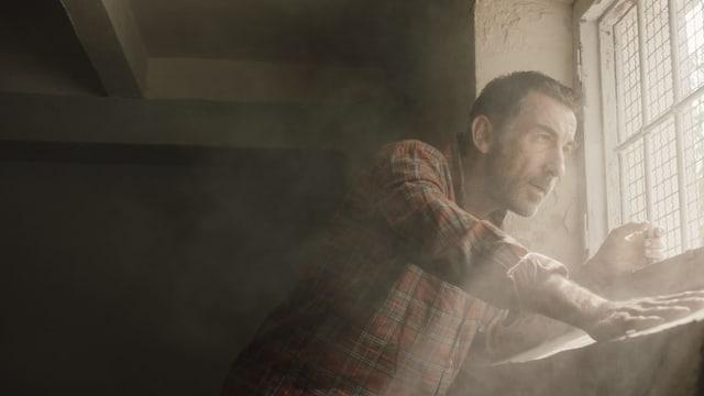 Mann steht in einem dunklen, staubigen Raum am Fenster, wo Licht hineinkommt.