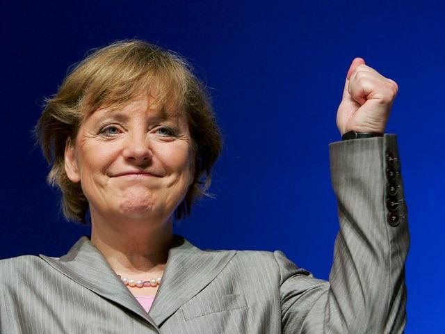 Angela Merkel streckt die Faust nach oben.