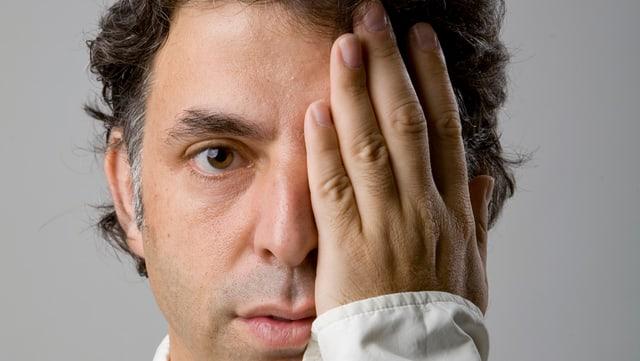 Portrait von Etgar Keret, er hält sich sein linkes Auge zu