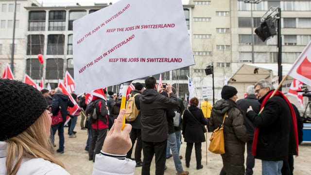 """Demonstrantin hält Plakat in die Höhre """"kee the Jobs in Switzerland"""""""