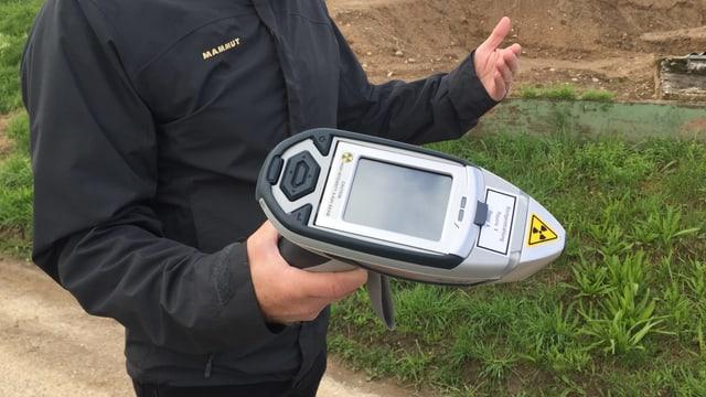 Mann hält ein Gerät in der Hand, das wie ein Scanner aussieht