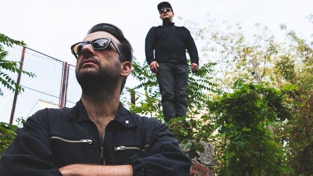 Modeselektor in Wiese mit Sonnenbrille und schwarzem Outfit