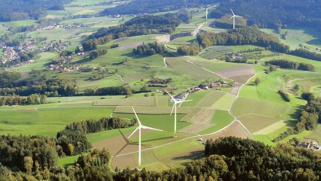 Eine Landschaft aus der Luft mit vier grossen modernen Windrädern.