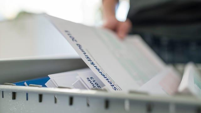 Jemand legt ein Steuererklärungsformular in ein Hängefach.