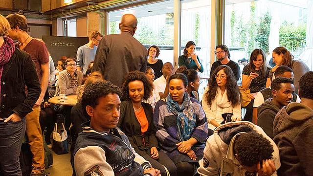 Menschen verschiedner Herkunft sitzen in einem Saal.