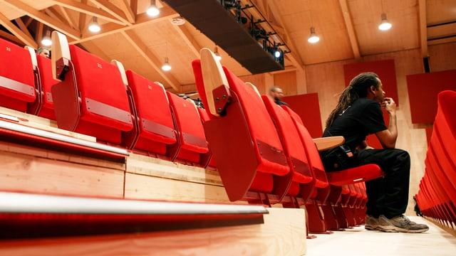 Eine rote Stuhlreihe in einem Holzbau, ganz vorne sitzt ein schwarz gekleideter Mann.