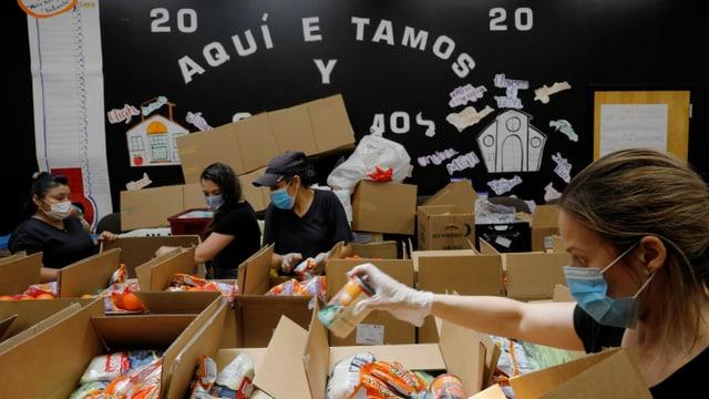 Hilfskräfte füllen Schachteln mit Gratis-Lebensmitteln.