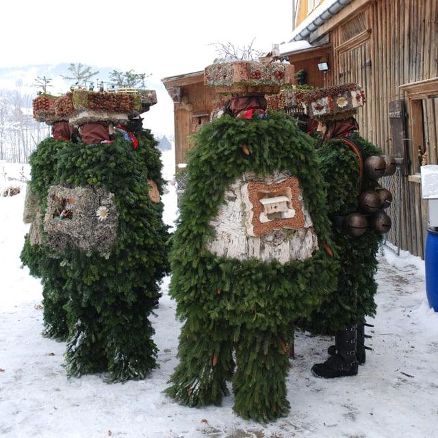 Mehrere mit Tannenzweigen und Hauben geschmückte Personen stehen im Schnee im Kreis.