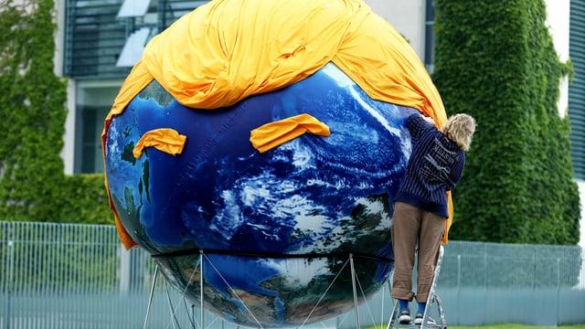 Eine Weltkugek ist mit einem gelben Tuch geschmückt, das die Frisur von Donald Trump darstellen soll.