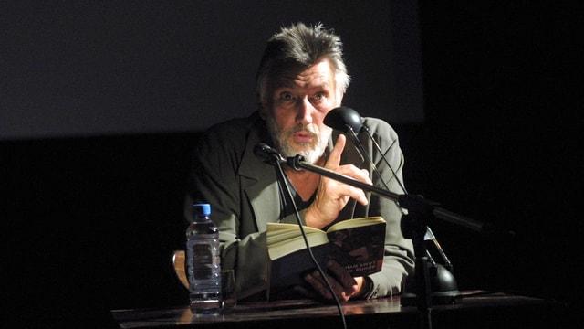 Mann im Licht eiener Leselampe: Er hält ein Buch, schaut auf und hebt den Zeigefinger.
