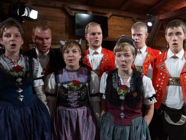 Jugendliche in Trachten singen.