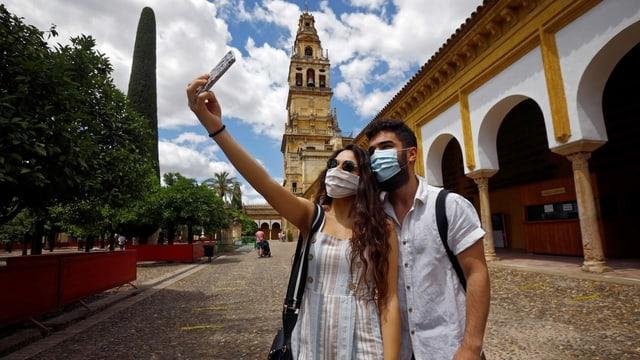 Zwei junge Personen mit Mundschutz machen Selfie in Cordoba.