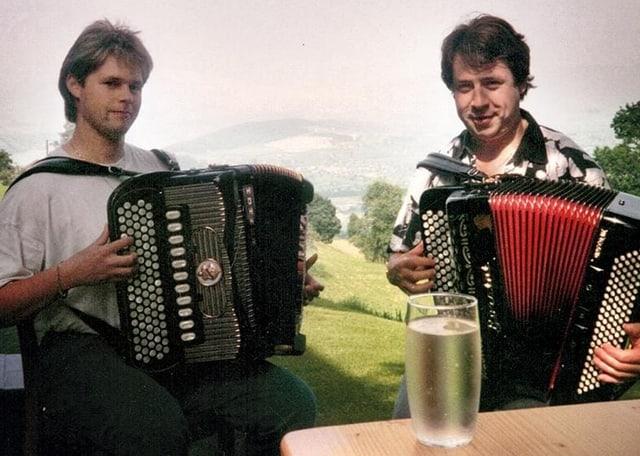 Zwei Akkordeonisten spielen auf Wiese.