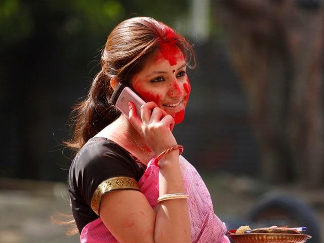 Eine Hindu-Frau hat Farbpulver in ihrem Gesicht während sie telefoniert. Sie nimmt an den Durga Puja Festlichkeiten in New Delhi teil.