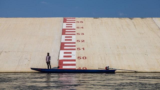 Ein Mann steht in einem Boot in einem Fluss. Dahinter eine grosse Mauer mit roten Ziffern, die die Wasserhöhe messen.