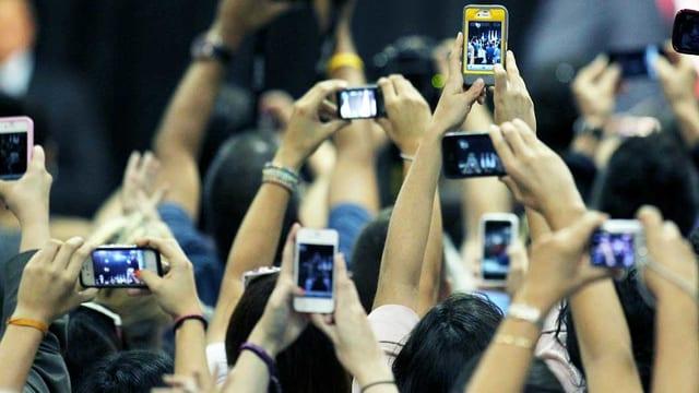 Viele Hände halten ein Smartphone in die Luft und filmen.