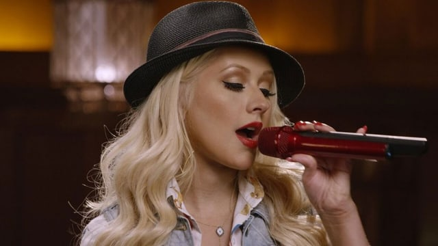 Christina Aguilera singt in ein Mikrofon. Sie trägt einen schwarzen Hut.