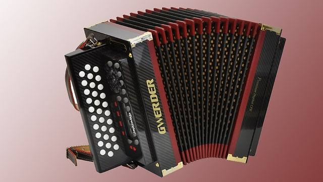 Schwarz-rotes Schwyzerörgeli aus dem Musikhaus Gwerder, die das traditionelle Instrument neuerdings aus Carbon anfertigt. Das Instrument auf einem blass-roten Hintergrund.
