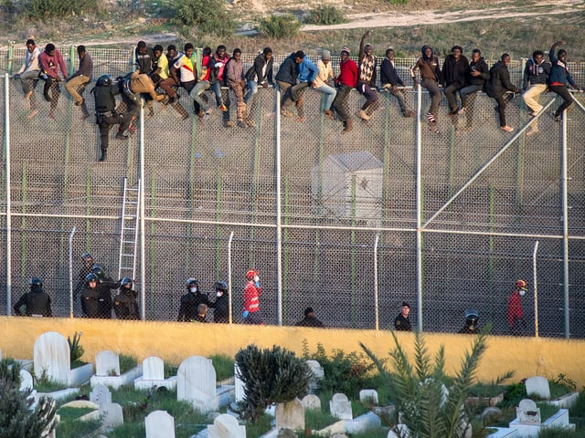 Flüchtlinge sitzen auf dem Grenzzaun im spanischen Melilla.