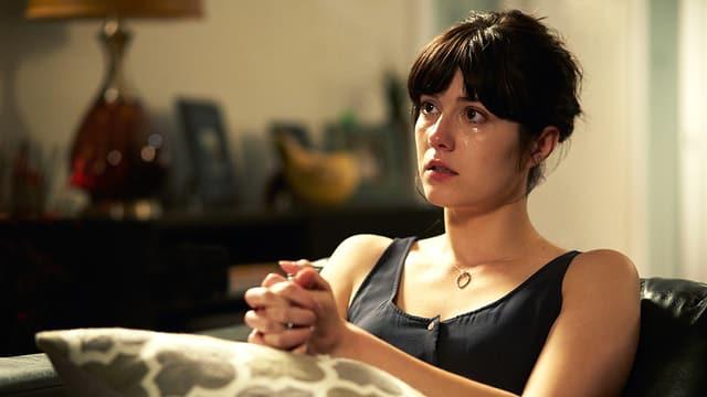 Eine Frau sitzt auf einem Sofa, sie weint.