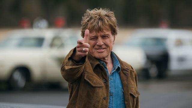 Robert Redford ahmt mit seiner Hand eine Pistole nach.