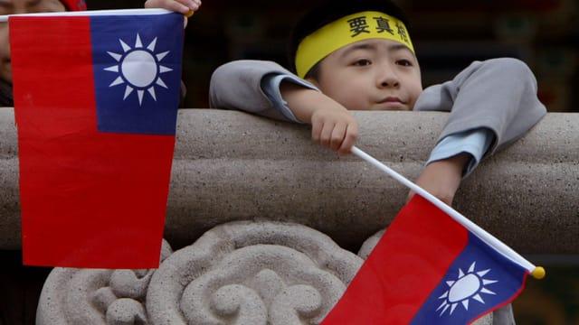 Ein Bub hält die Flagge von Taiwan in den Händen.