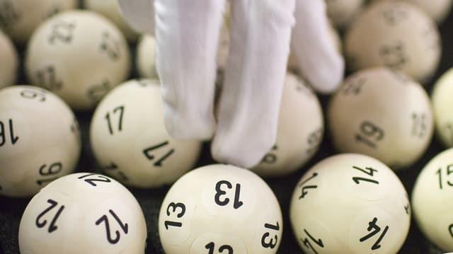 Finger in einem weissen Handschuh berühren aneinanderliegende Lottokugeln, in der Mitte: Nummer 13.