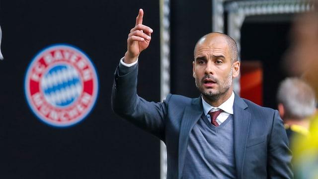 Bayern-Coach Pep Guardiola steht mit erhobenem Zeigefinger an der Seitenlinie.