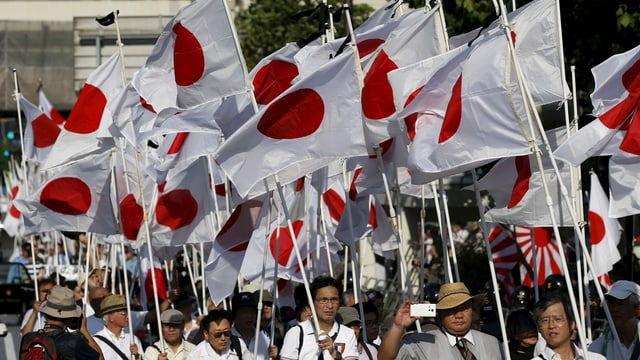 Männer paradieren mit japanischen Flaggen auf einer Strasse.