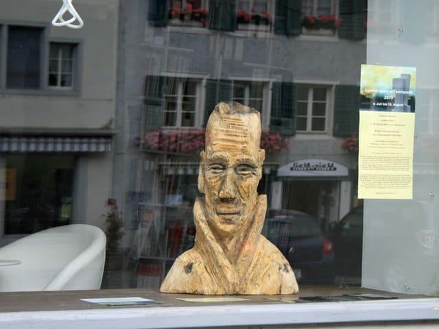 Eine Holzskulpur steht im Schaufenster.