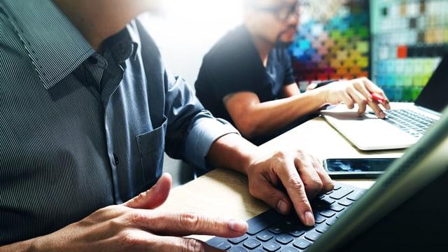 Zwei Männern arbeiten an Laptops.